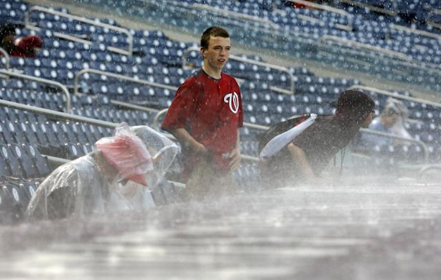 A few fans brave the rain during a rain delay in the sixth inning of a baseball game between the Washington Nationals and the Cincinnati Reds at Nationals Park on Wednesday, May 21, 2014, in Washington. (AP Photo/Alex Brandon)