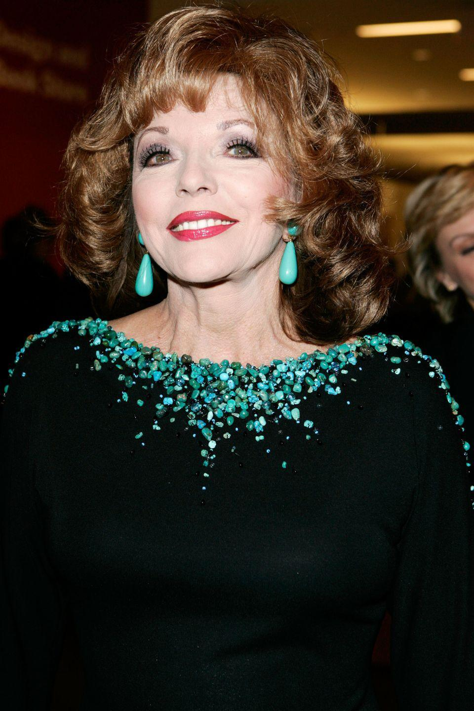 <p>Matching her turquoise drop earrings to the dramatic neckline of her dress for a night at the museum.</p>