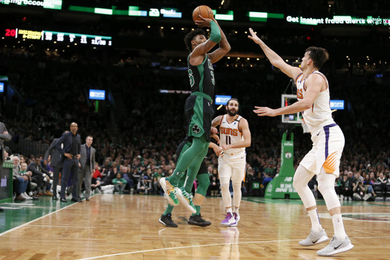 Boston Celtics guard Marcus Smart (36) shoots a three-point shot over Phoenix Suns forward Dario Saric (20) during the second half of an NBA basketball game, Saturday, Jan. 18, 2020, in Boston. (AP Photo/Mary Schwalm)