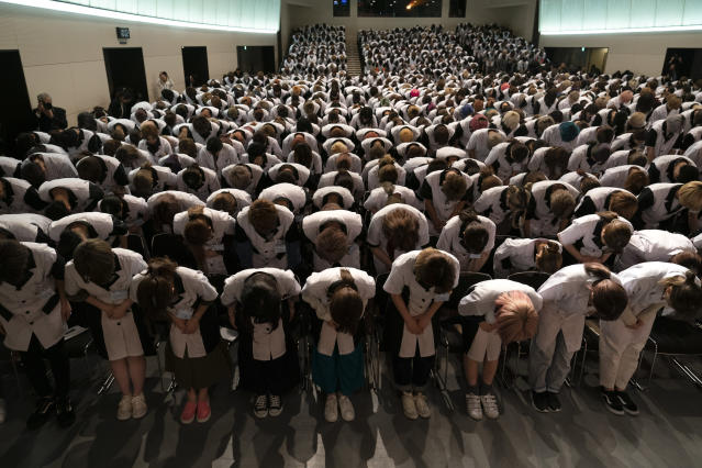 Wearing school uniforms, students at Yamano Beauty College bow to a speaker during a ceremony held to celebrate the school's 83rd year anniversary in Tokyo, May 31, 2019. More than 1,200 students from all over Japan are attending the school to be hair stylists or makeup artists. (AP Photo/Jae C. Hong)