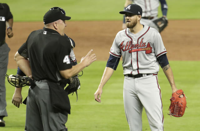Home plate umpire Jeff Nelson, left, talks with Atlanta Braves starting pitcher Kevin Gausman after Gausman was ejected for throwing at Miami Marlins' Jose Urena during the second inning of a baseball game Friday, May 3, 2019, in Miami. (AP Photo/Lynne Sladky)