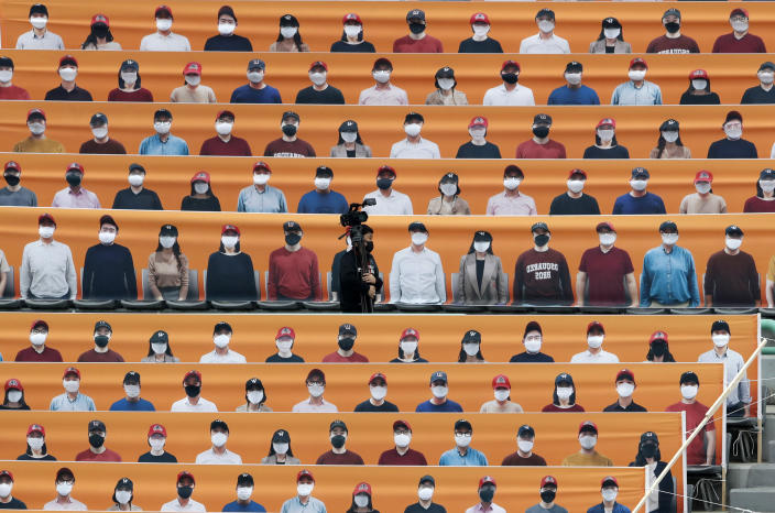 A TV cameraman walks through the spectators' seats which are covered with pictures of fans, before the start of a regular season baseball game between Hanwha Eagles and SK Wyverns in Incheon, South Korea, Tuesday, May 5, 2020. South Korea's professional baseball league start its new season on May 5, initially without fans, following a postponement over the coronavirus. (AP Photo/Lee Jin-man)