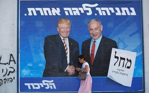 A woman walks past a Likud party election campaign banner depicting Israeli Prime Minister Benjamin Netanyahu and Donald Trump in Tel Aviv - Credit:  CORINNA KERN/ REUTERS