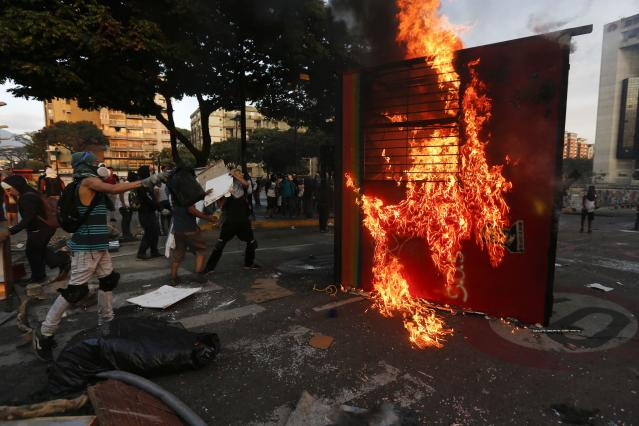 Anti-government protesters throw flammable items into a burning kiosk, used as barricade, during a protest in Caracas March 9, 2014. Latin American foreign ministers will meet next week to discuss the unrest in Venezuela that has left at least 20 dead and convulsed the South American OPEC nation, diplomatic sources said on Friday. REUTERS/Tomas Bravo (VENEZUELA - Tags: POLITICS CIVIL UNREST)