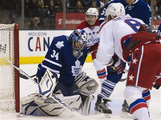 Toronto Maple Leafs goalie James Reimer, left, makes a save on a shot by Washington Capitals forward Alexander Ovechkin, right, during first-period NHL hockey game action in Toronto, Saturday, Feb. 25, 2012. (AP Photo/The Canadian Press, Nathan Denette)