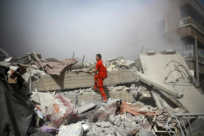 A member of the Syrian Red Crescent inspects rubble searching for victims in the rebel-held area of Douma, following shelling and air raids by Syrian government forces on August 22, 2015. (AFP Photo/Abd Doumany)