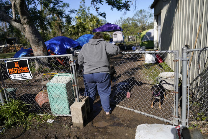 Sherry Bourque enters the back yard of her fathers heavily damaged home, where she is living in a tent, in the aftermath of both Hurricane Laura and Hurricane Delta, in Lake Charles, La., Friday, Dec. 4, 2020. (AP Photo/Gerald Herbert)