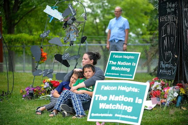 """<p>Kate Khaled, of St. Paul, Minn., and her two sons, Jibreel, 8, left, and Esa, 7, sit Friday, June 16, 2017, at the memorial near the site where Philando Castile was shot and killed during a traffic stop by St. Anthony police Officer Jeronimo Yanez last July. The two boys went to J.J. Hill Montessori and knew """"Mr. Phil."""" Yanez was cleared Friday in the fatal shooting of Castile, a black motorist whose death captured national attention when his girlfriend streamed the grim aftermath on Facebook. (Aaron Lavinsky/Star Tribune via AP) </p>"""