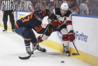 New Jersey Devils' Taylor Hall (9) and Edmonton Oilers' Matt Benning (83) compete for the puck during the first period of an NHL hockey game Friday, Nov. 8, 2019, in Edmonton, Alberta. (Jason Franson/The Canadian Press via AP)