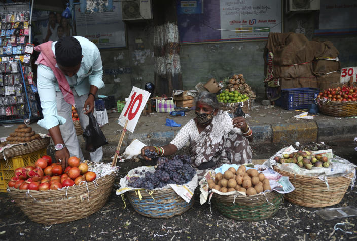 A fruit vendor waits for customers in Hyderabad, India, Friday, June 11, 2021. India's economy was on the cusp of recovery from the first pandemic shock when a new wave of infections swept the country, infecting millions, killing hundreds of thousands and forcing many people to stay home. Cases are now tapering off, but prospects for many Indians are drastically worse as salaried jobs vanish, incomes shrink and inequality is rising. (AP Photo/Mahesh Kumar A.)