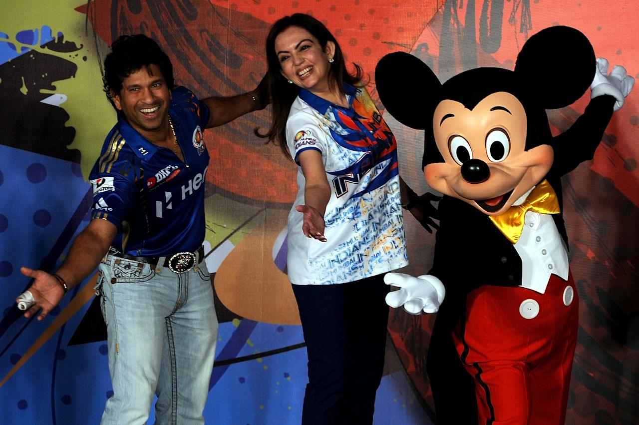 "Mumbai Indians cricketer Sachin Tendulkar (L) and team owner Nita Ambani (C) pose with Disney character Mickey Mouse (R) during an event to unveil ""Mickey Cricket"", a limited edition merchandise range, in Mumbai on April 5, 2012. The collection from Disney Consumer Products, the business segment of The Walt Disney Company, includes accessories, toys and clothing featuring Disney characters.  AFP PHOTO/Indranil MUKHERJEE (Photo credit should read INDRANIL MUKHERJEE/AFP/Getty Images)"