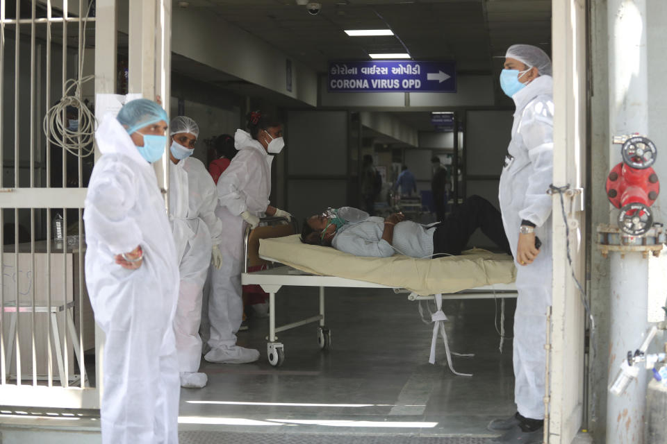 FILE - In this April 15, 2021, file photo, health workers carry a patient into a dedicated COVID-19 hospital in Ahmedabad, India. The picture is still grim in parts of Europe and Asia as variants of the virus fuel an increase in new cases and the worldwide death toll closes in on 3 million. (AP Photo/Ajit Solanki, File)