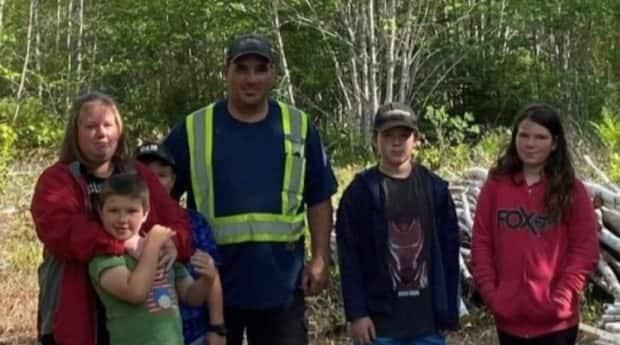 Elaine Heighton, left, stands with her husband, Quincy, and their four children on the lot in the village of Tatamagouche, N.S., about 50 kilometres north of Truro, where community members volunteered to build them a new house after they became homeless. (Friends of the Heightons/GoFundMe - image credit)