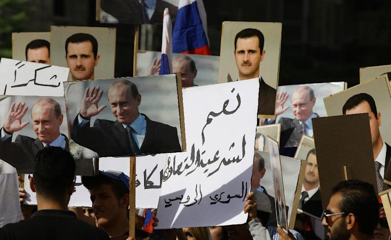 Several hundred people, holding up portraits of Syrian President Bashar al-Assad and his Russian counterpart Vladimir Putin (L), gather near the Russian embassy in Damascus on October 13, 2015 to express their support for Moscow's air war in Syria (AFP Photo/Louai Beshara)