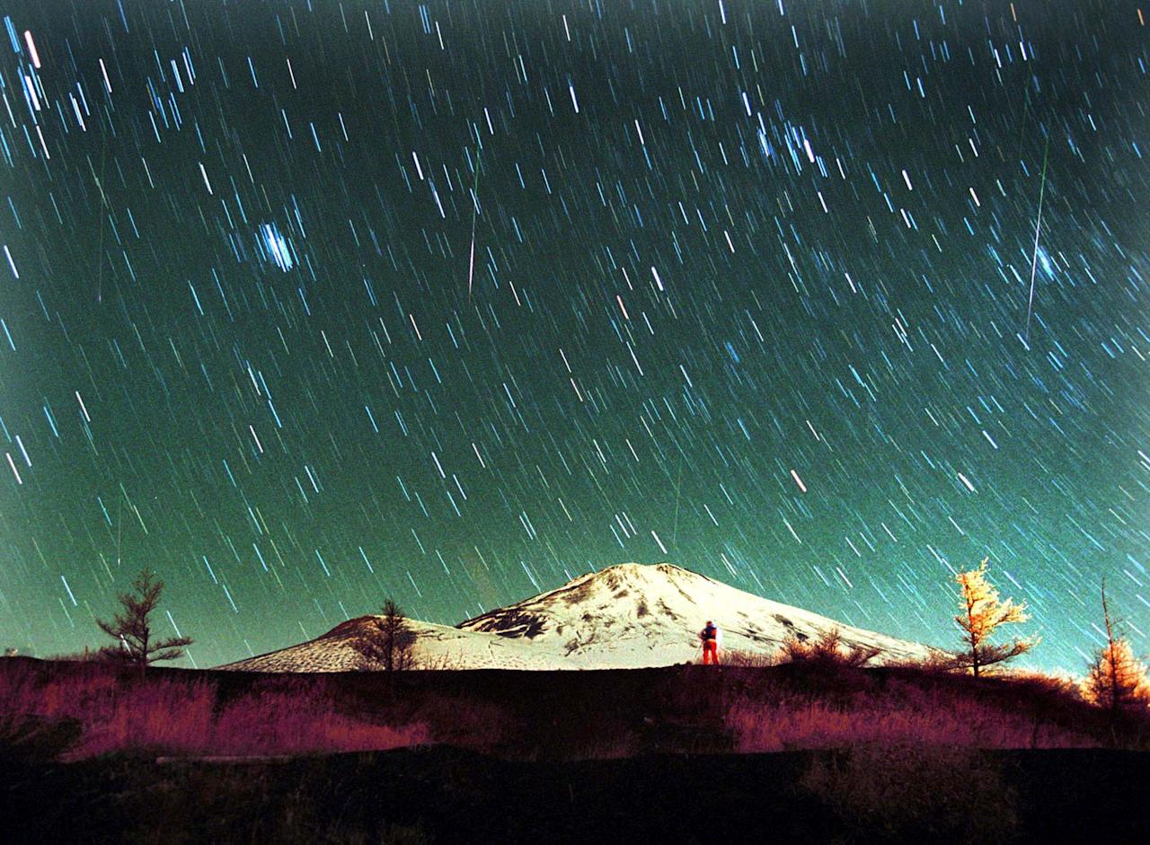 Leonid meteors are seen streaking across the sky over snow-capped Mount Fuji, Japan's highest mountain, early Monday Nov. 19, 2001, in this 7-minute exposure photo. Star gazers braved cold temperatures at the foot of Mount Fuji to observe the shower of Leonid meteors. (AP Photo/Itsuo Inouye)