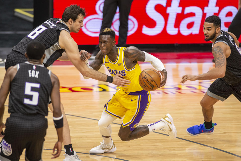 Los Angeles Lakers guard Dennis Schroder (17) drives to the basket as Sacramento Kings forward Nemanja Bjelica (8) reaches for the ball in the second quarter of an NBA basketball game in Sacramento, Calif., Wednesday, March 3, 2021. (AP Photo/Hector Amezcua)