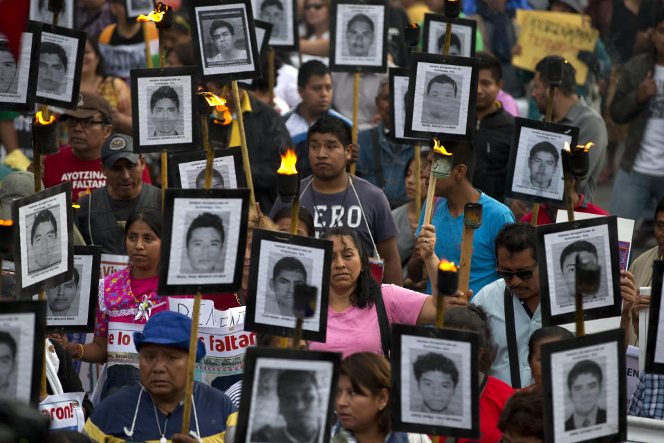 FILE - In this April 26, 2016 file photo, family members and supporters of 43 missing teachers college students carry pictures of the students as they march to demand the case not be closed and that experts' recommendations about new leads be followed, in Mexico City. Nearly six years after 43 students disappeared in Mexico's southern Guerrero state, Attorney General Alejandro Gertz Manero said Tuesday, June 30, 2020 that prosecutors had requested 46 arrest warrants for various municipal level public servants in the state in relation to the case. (AP Photo/Rebecca Blackwell, File)