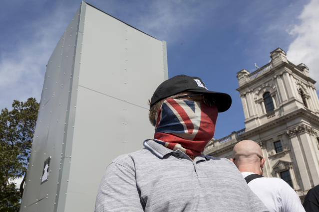 A right-wing protester stands next to the boxed-in statue of Winston Churchill over the weekend (Getty)