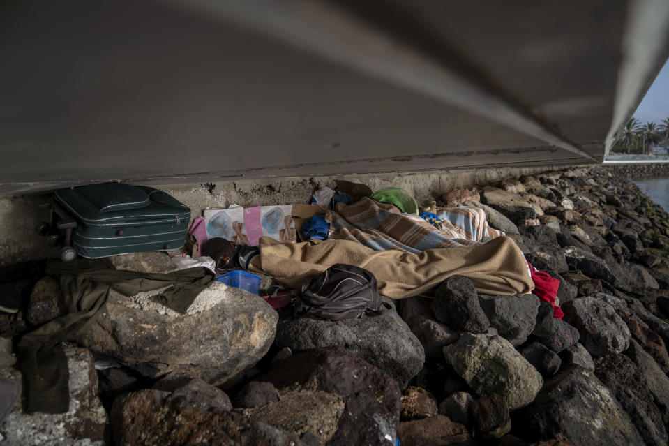 Khalid, a migrant from Gambia, sleeps on a breakwater under a bridge in Gran Canaria island, Spain, on Saturday, Aug. 22, 2020. The striking shift in migration back to the Canary Islands has raised alarms at the highest levels of the Spanish government. (AP Photo/Emilio Morenatti)