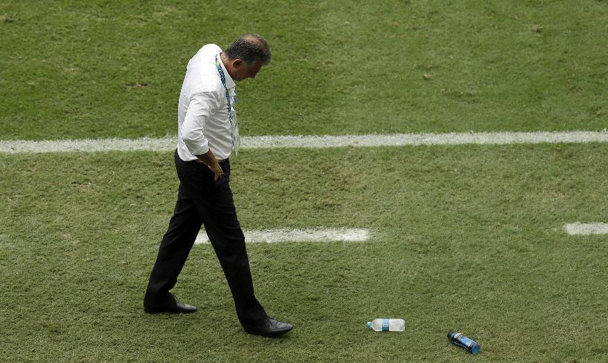 Iran coach Carlos Queiroz kicks a water bottle after Bosnia midfielder Miralem Pjanic's goal during the second half of a group F World Cup soccer match at the Arena Fonte Nova in Salvador, Brazil, Wednesday, June 25, 2014. (AP Photo/Themba Hadebe)