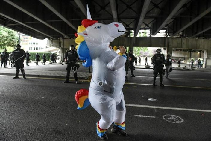 A person dressed as a unicorn dances in front of police officers during a far-right rally on August 17 in Portland, Oregon (AFP Photo/STEPHANIE KEITH)
