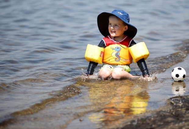 Niko Allin, seen here playing in the water near Westboro Beach last July, can return for more as of June 19. (Andrew Lee/CBC - image credit)