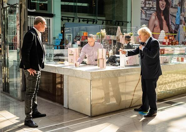 Britain's Prime Minister Boris Johnson buys a coffee from Freddy Staple, operations manager for Caffe Concerto at Westfield shopping centre in east London.