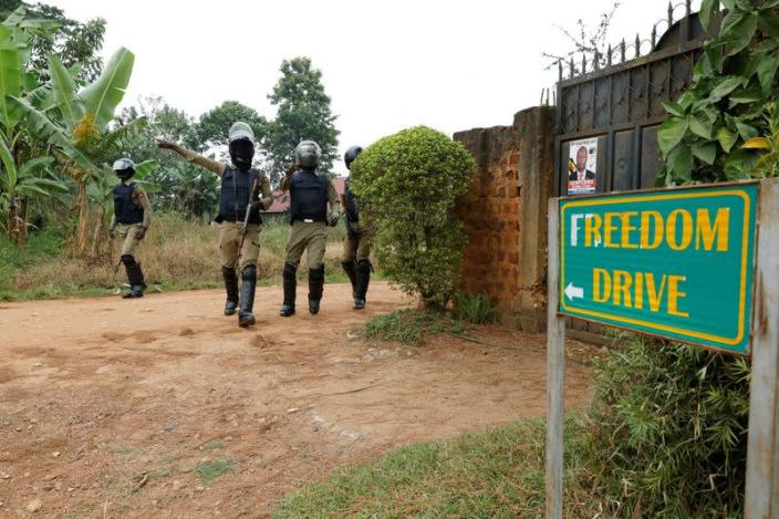 FILE PHOTO: Ugandan police officers order journalists to leave a road leading to the home of Ugandan opposition presidential candidate Robert Kyagulanyi, also known as Bobi Wine, in Kampala