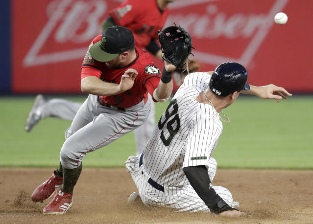 Los Angeles Angels second baseman Zack Cozart, left, is unable to catch a throw from catcher Jose Briceno on a stolen base by New York Yankees' Aaron Judge during the third inning of a baseball game Saturday, May 26, 2018, in New York. Judge moved to third on the play. (AP Photo/Julio Cortez)