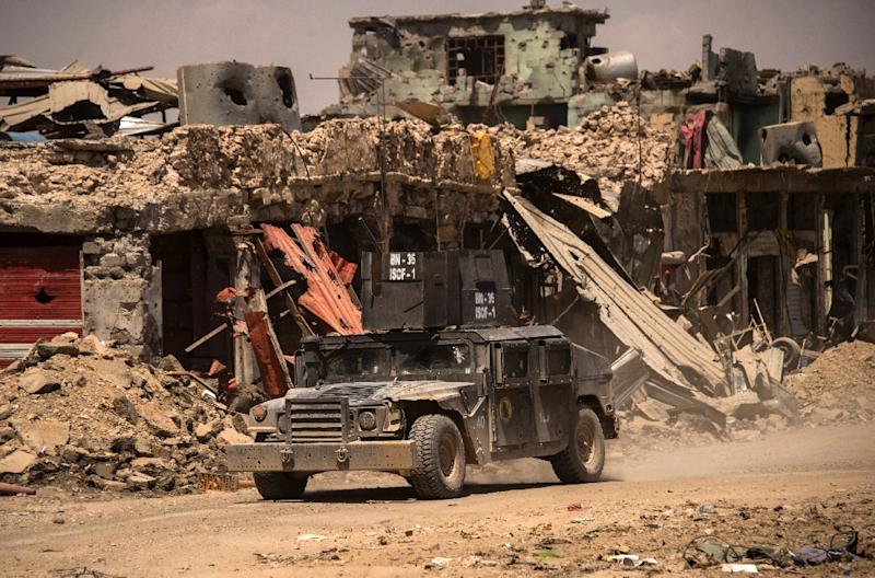 Iraqi forces patrol a street in west Mosul on July 12, 2017