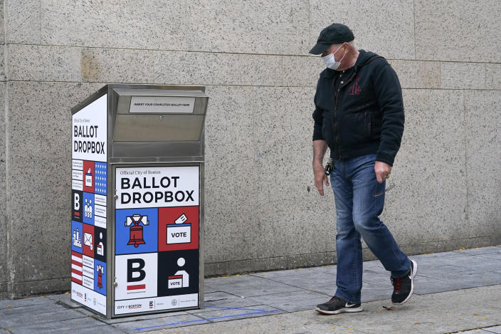 """A pedestrian walks by the ballot drop box outside the Boston Public Library, Monday, Oct. 26, 2020, in Boston. Massachusetts election officials say a fire was set in the ballot drop box Sunday, holding more than 120 ballots in what appears to have been a """"deliberate attack."""" The FBI says it is investigating. (AP Photo/Elise Amendola)"""