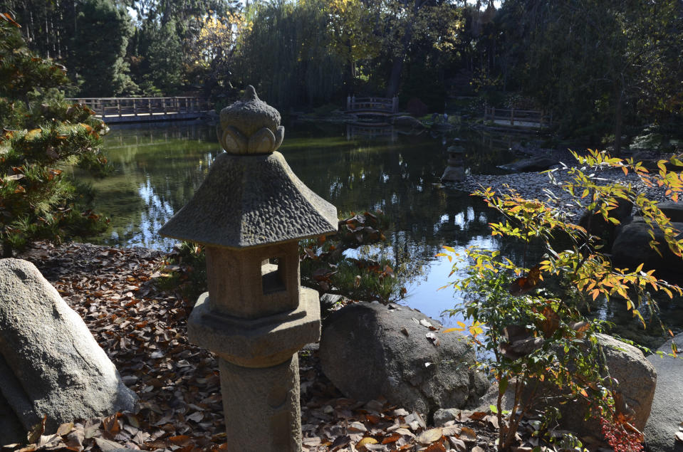 A Japanese-style stone lantern stands next to a footpath with a view to the central pond in the Japanese Garden at Lotusland, Monday, Nov. 23, 2020, in Montecito, Calif. The Japanese Garden recently underwent a $6 million renovation. (AP Photo/Pamela Hassell)