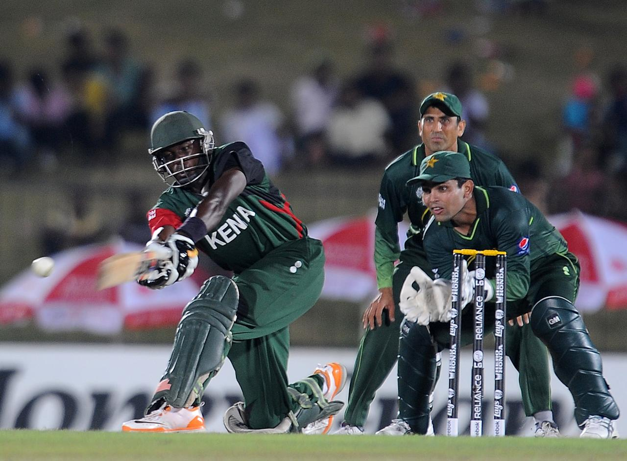 Kenyan cricketer Steve Tikolo (L) is watched by Pakistani wicketkeeper Kamran Akmal (R) and captain Younis Khan (TOP) as he plays a shot during the Group A match in the World Cup Cricket tournament between Pakistan and Kenya at The Suriyawewa Mahinda Rajapakse International Cricket Stadium in the southern district of Hambantota on February 23, 2011. Kenya are 79 runs for the loss of three wickets in fourteen overs as they chase the Pakistan total of 317. AFP PHOTO/Lakruwan WANNIARACHCHI