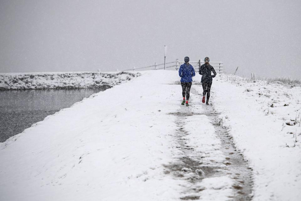 Two women run in snowy conditions alongside Brun Clough Reservoir as snow falls above the village of Delph, near Manchester in northern England on December 4, 2020. (Photo by OLI SCARFF / AFP) (Photo by OLI SCARFF/AFP via Getty Images)