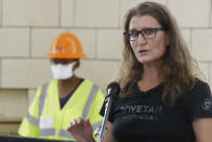 """FILE - In this Friday, July 17, 2020 file photo, Kary Stackelbeck, state archaeologist, speaks during a news conference as work continues on an excavation of a potential unmarked mass grave from the 1921 Tulsa Race Massacre, at Oaklawn Cemetery, in Tulsa, Okla. """"If the boundaries we estimate are accurate, what we excavated in October is maybe a third or a quarter of that overall size,"""" she says. """"It is not unreasonable for us to develop an estimate of around 30 total (bodies) in the overall mass grave, and that's a conservative estimate."""" (AP Photo/Sue Ogrocki, File)"""