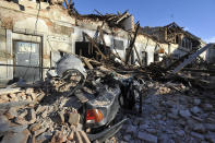 A view of remains of a car covered by debris and buildings damaged in an earthquake in Petrinja, Croatia, Tuesday, Dec. 29, 2020. A strong earthquake has hit central Croatia and caused major damage and at least one death and 20 injuries in a town southeast of the capital Zagreb. (AP Photo)