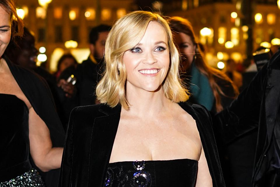 Reese Witherspoon wears an off-shoulder dress and a black velvet jacket, outside Armani, during Paris Fashion Week - Haute Couture Spring/Summer 2020, on January 21, 2020 in Paris, France. (Photo by Edward Berthelot/Getty Images )é