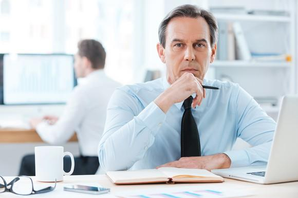 Man in business attire sitting at a desk.