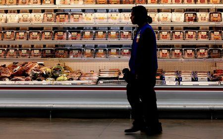 FILE PHOTO - A employee walks by a meat cooler in the grocery section of a Sam's Club in Bentonville
