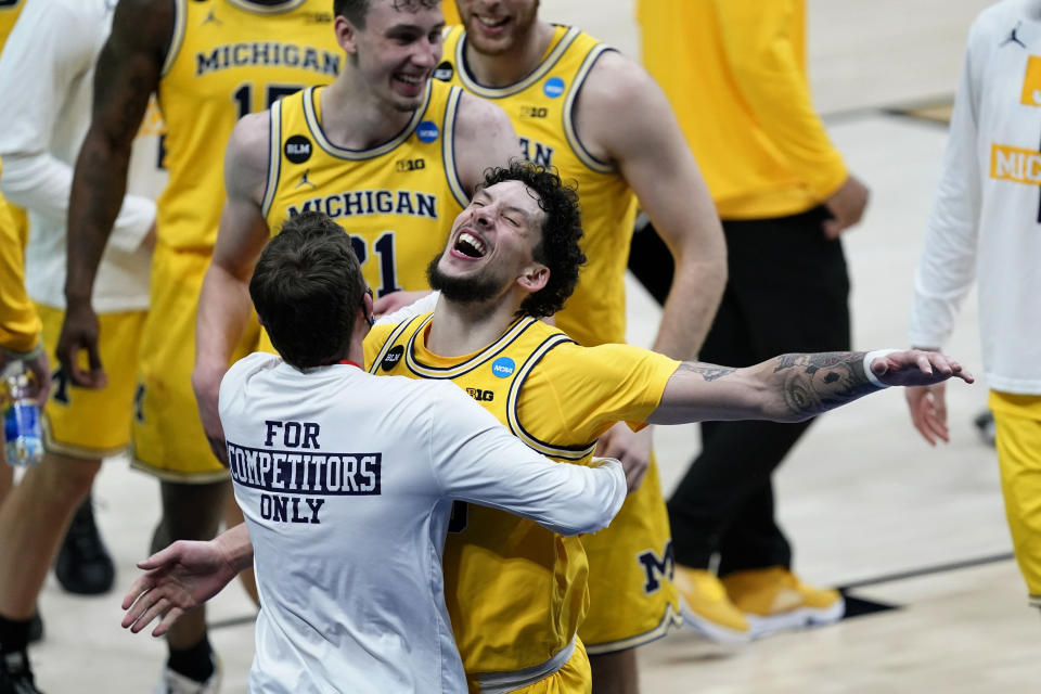 Michigan forward Brandon Johns Jr. celebrates with teammates after a second-round game against LSU in the NCAA men's college basketball tournament at Lucas Oil Stadium Monday, March 22, 2021, in Indianapolis. Michigan won 86-78. (AP Photo/AJ Mast)