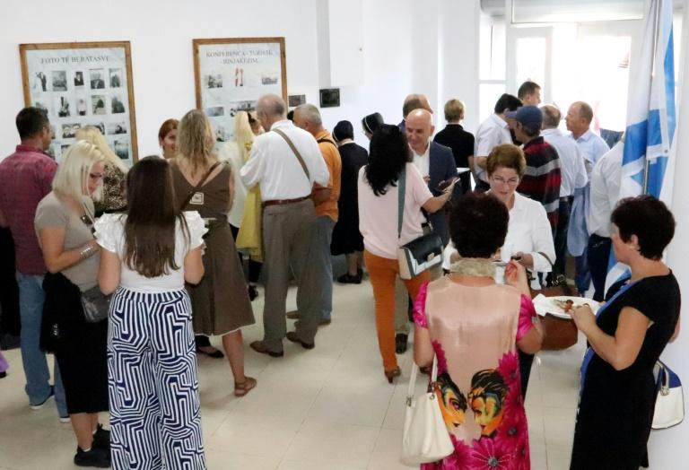 """Visitors attend the opening ceremony of the renovated Solomon Jewish history museum in the Albanian city of Berat, on September 29, 2019.Albania's sole Jewish history museum reopened in southern Berat on September 29, thanks to a businessman who rescued it from the brink of closure. The small """"Solomon Museum"""", which tells the story of how Muslim and Christian Albanians sheltered hundreds of Jews during the Holocaust, was the passion project of a local professor, Simon Vrusho. (AFP Photo/STRINGER)"""