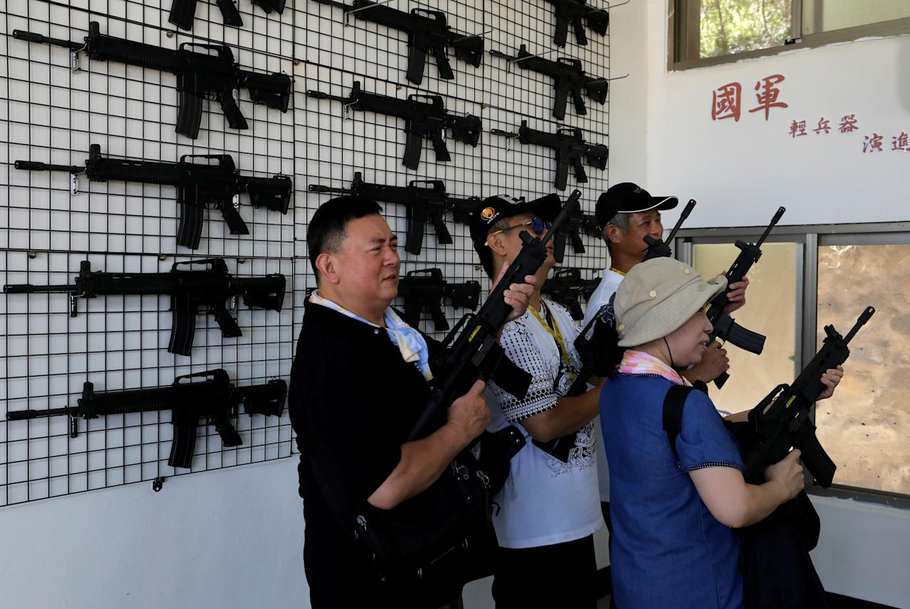 Tourists take part in an electronic shooting game, simulating the 1958 attacks, ahead of the 60th anniversary of Second Taiwan Straits Crisis against China, on Lieyu island, Kinmen county, Taiwan August 20, 2018. REUTERS/Tyrone Siu