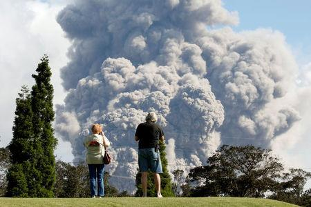 FILE PHOTO: People watch ash erupt from the Halemaumau Crater near the community of Volcano during ongoing eruptions of the Kilauea Volcano in Hawaii, U.S., May 19, 2018.  REUTERS/Terray Sylvester/File Photo