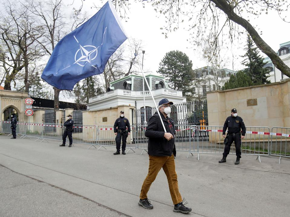 A man carrying a Nato flag to protest over Russian intelligence services' alleged involvement in an ammunition depot explosion in the Vrbetice area in 2014 walks past police officers outside the Russian embassy in Prague, 18 April 2021David W Cerny/Reuters