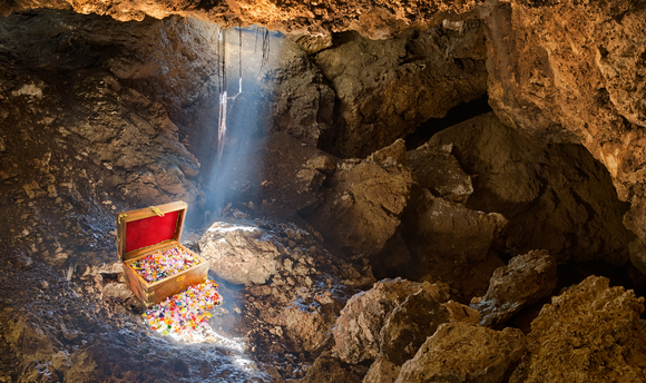 A single beam of sunlight enters a dark cave, illuminating a treasure chest brimming with gold and jewelry.