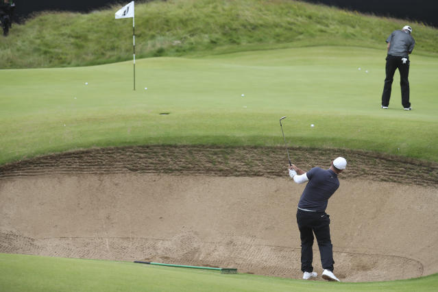 Brooks Koepka of the United States, bottom right, chips out of a bunker as Dustin Johnson of the United States putts on the 17th green during a practice round ahead of the start of the British Open golf championships at Royal Portrush in Northern Ireland, Wednesday, July 17, 2019. The British Open starts Thursday. (AP Photo/Peter Morrison)