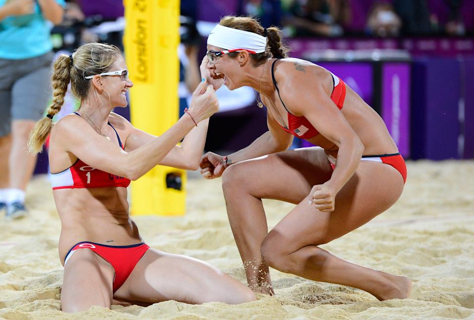 Misty May-Treanor and Kerri Walsh (left) celebrate winning the gold medal after defeating April Ross and Jennifer Kessy (USA) in the women's beach volleyball gold medal match during the 2012 London Olympic Games.