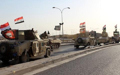 A convoy of Iraqi military trucks flying religious Shia flags and Iraqi national flag as they advance into the central of Kirkuk city, northern Iraq - Credit: EPA