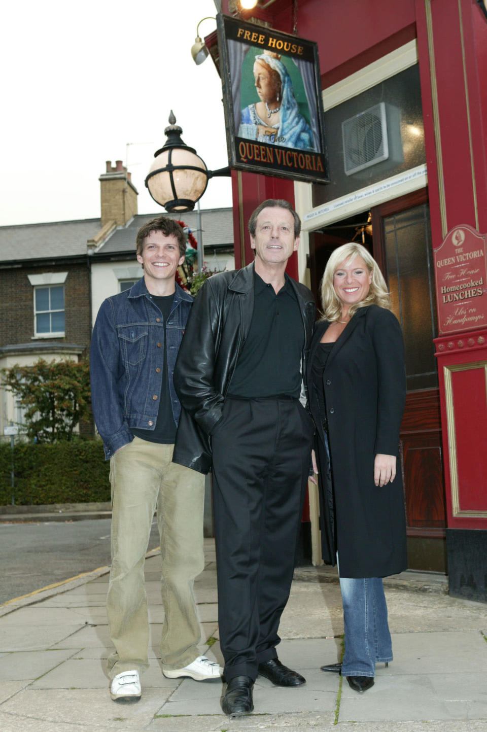 Leslie Grantham (C), Nigel Harman (L) and actress Letitia Dean pose outside the Queen Vic pub on the Eastenders set to promote their new storyline featuring the return of Dirty Den, at Elstree Studios on September 28, 2003 in London. (Photo by Rod Johnson/Getty Images)