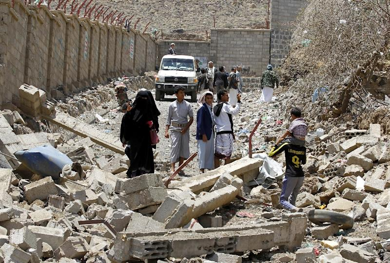 Yemenis walk in the rubble of destroyed buildings in the Al-Nahda neighbourhood of Sanaa, following intensified Saudi-led coalition air strikes, on September 6, 2015 (AFP Photo/Mohammed Huwais)